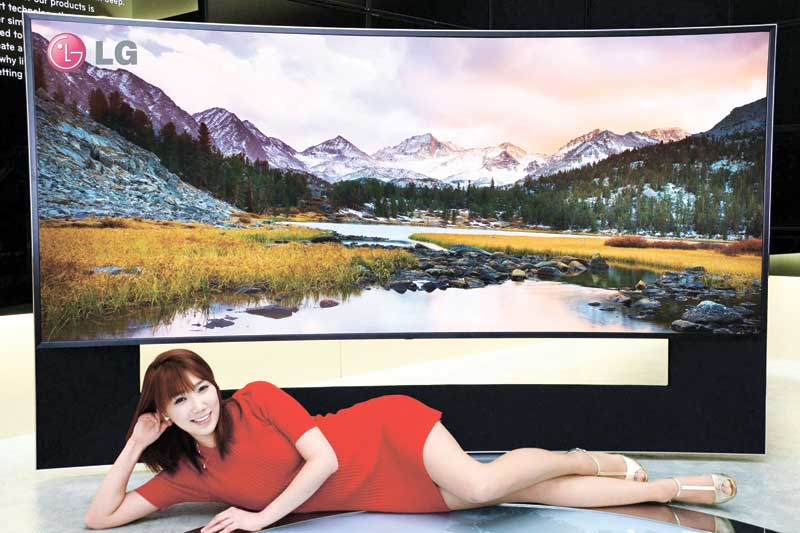 A model feels relaxed in front of an LG Electronics' 105-inch ultra-HD TV with curved screen
