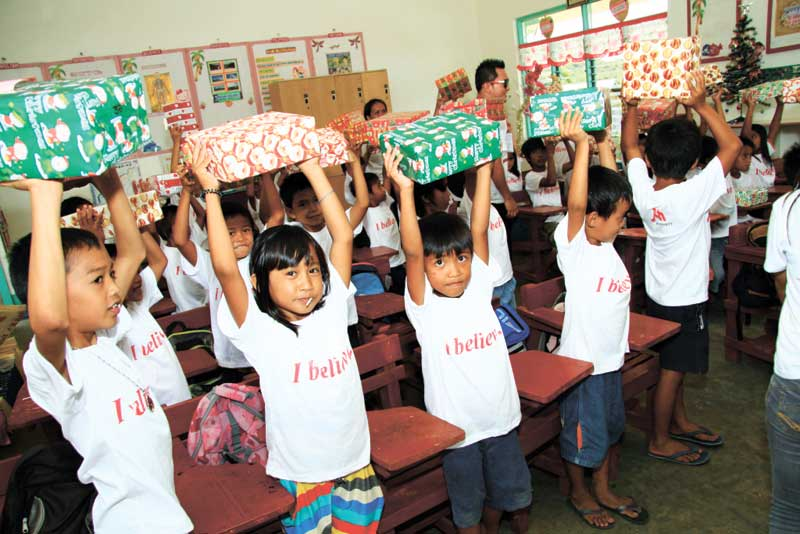 Kids of Taba-ao happily raise their Christmas shoeboxes filled with toys and goodies.
