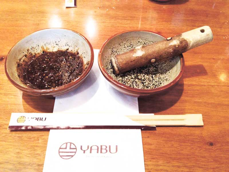 YABU RITUAL. While waiting for the food, diners crush their own sesame seeds and mix in the katsu sauce.