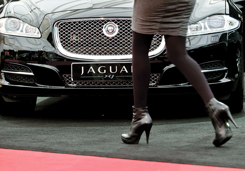 NOT JUST FOR MEN. A woman passes by a Jaguar XJ during an Auto Moto Show in Bucharest, Romania. Women now buy nearly half the new cars in the United States, a sharp increase compared with a generation ago, and the auto industry is trying to demonstrate that it's keeping up with the times when it showcases the latest models to the public. (AP FOTO)