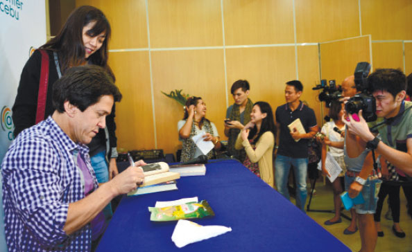 LAUNCHING BOOKS AND BOATS. Mitch Albom signs books during a press conference. Albom said he, in partnership with National Book Store, donated 40 fishing boats to Typhoon Yolanda survivors in Tacloban City and initiated a drive to rebuild 10 libraries in the region. He will restock the library with books from his personal collection, as well as from his writer-friends who have pledged to help, including Stephen King, Nicholas Sparks, Khaled Hosseini, John Grisham, Dave Patterson, Suzanne Collins and Lemony Snicket.