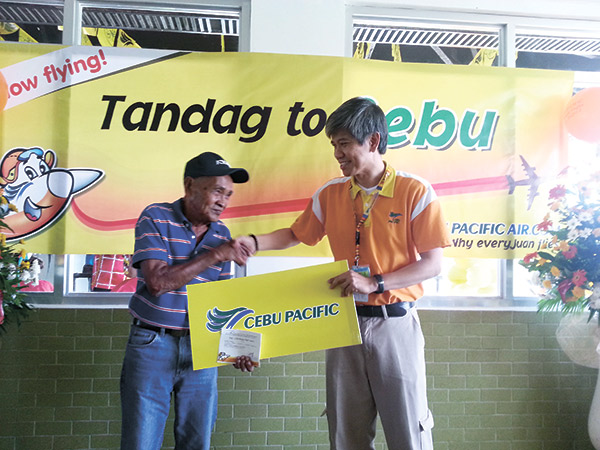 Cebu Pacific, represented by Junard Cruz, awards the first checked-in passenger with a complementary round-trip ticket.