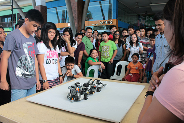 ROBOT CHEER. Spectators and competing teams cheer on the robots during the elimination round.