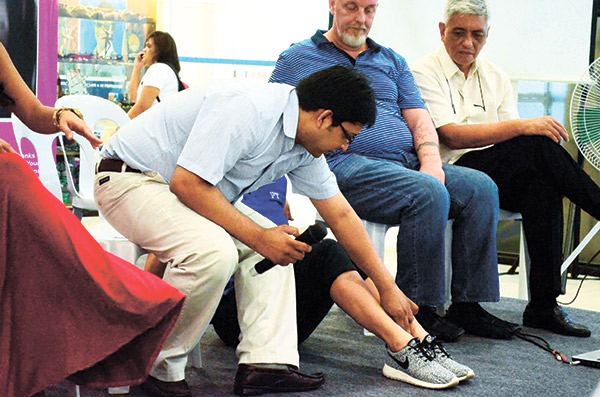Dr. Ajay Yadav demonstrates how to determine imbalanced feet, a possible sign of scoliosis.