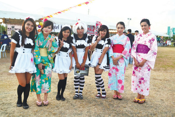 Cosplayers in maid costumes and kimonos