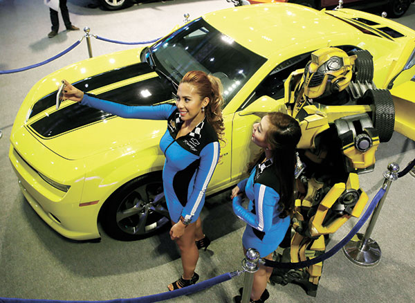 """SELFIE WITH A CHEVY. Models take a selfie with """"Bumble Bee,"""" which transforms into a Chevrolet Camaro RS in the movie Transformers, at the 2015 Manila International Auto Show. The annual auto show held from April 9 to 12 at the World Trade Center in Pasay city featured more than 500 cars and trucks and over 90 bikes and motorcycles from 30 different brands. (AP FOTO)"""