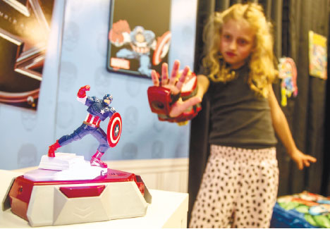 """ROLE PLAYING. Actress Evangeline Lindes role demonstrates a Playmation """"repulsor"""" a wearable forearm attachment that puts kids in the role of Marvel superhero Iron Man, that connects via sensors with a base station called a """"power activator."""" (AP FOTO)"""