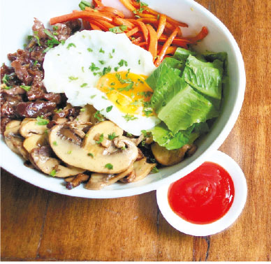 A more savory, spicy version of the classic Bibimbap has beef tips, carrots, shiitake and champignon mushrooms, fresh greens and a pan-fried egg resting on a mountain of Gochujang Fried Rice.
