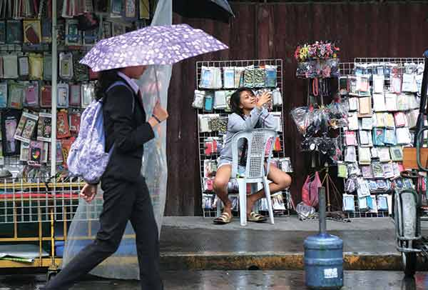 WET SEASON. A street vendor smiles as she takes a selfie on her smartphone near a university in Manila. While the vendor has something to smile about, Millions of commuters and vehicle owners all over the country, Metro Cebu included, will have to brace themselves for floods brought about by heavy rains and poor infrastructure. (AP FOTO)