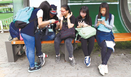 GENERATION APP. South Korean middle school students use their smartphones at a bus station in Seoul, South Korea. Do they mind that their parents are possibly monitoring their smartphone use through mobile apps? (AP FOTO)