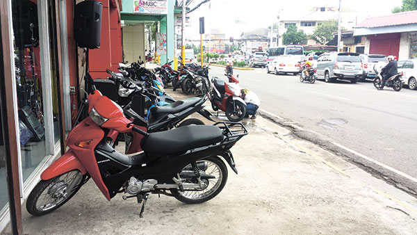 PARK AND DRIVE ANYWHERE. Two rows of motorcycles block and use the sidewalk along P. del Rosario St. as a display, parking and washing area. Notice, too, a motorcycle that's counterflowing on the left lane even if it's approaching the center island. (WEEKEND FOTO/ FREON L. OLLIVAL)