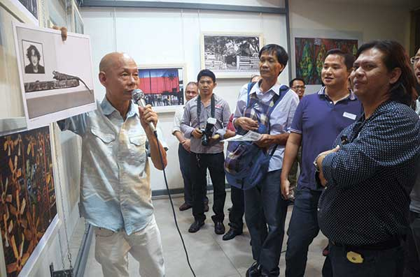 GLIMPSE. Bob Lim explains one of his exhibited works to select guests at the opening. (Weekend photo/Ruel Rosello)