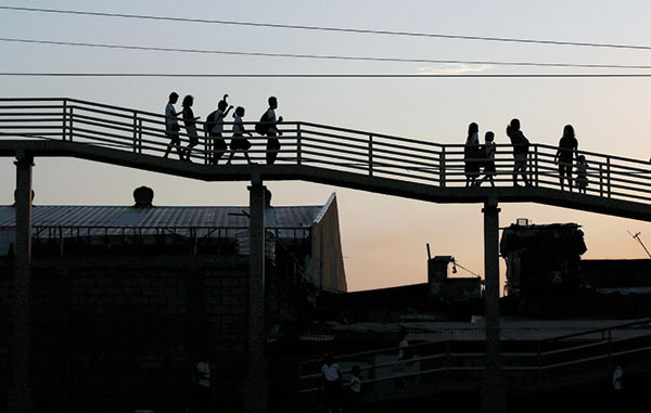 WORRY-FREE WALK. This image of residents walking unhurriedly along a pedestrian bridge in Metro Manila belies the terrible traffic situation that afflicts the entire metropolis, owing to poor infrastructure and government neglect. (AP FOTO)