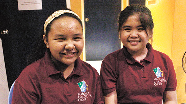 UNFORGETTABLE FEAT. Mandaue Children's Choir members Raya Paguio and Cher Lozada, both 11, are all smiles, happy to be members of an illustrious team of homegrown talents. (WEEKEND PHOTO/DENEB BATUCAN)