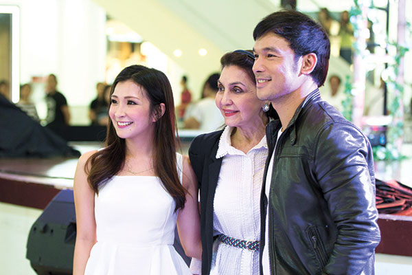 "ICONS. Stars of Resorts World Manila's ""Bituing Walang Ningning: The Musical"" Mark Bautista (right) and Monica Cuenco (left) flank Cebu society icon Amparito Llamas Lhuillier during the production's mall show at the activity area of Ayala Center Cebu. (CONTRIBUTED PHOTO)"