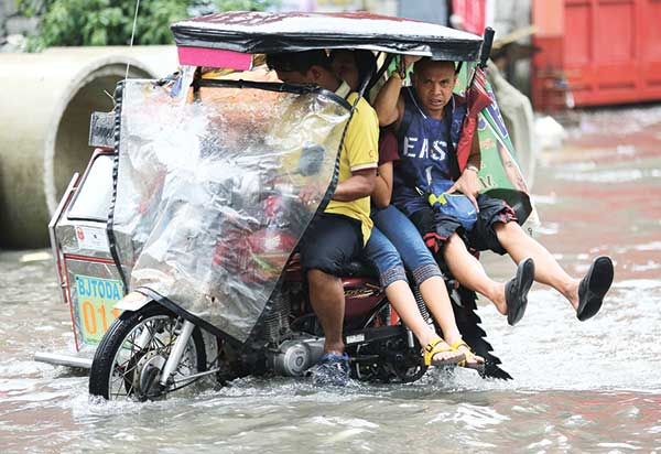 LIFT. Passengers on board a tricycle lift their feet to avoid floodwaters caused by heavy rains in Metro Manila. Heavy downpours have frequented the capital and other metro areas in the country almost daily, causing traffic jams and floods. (AP PHOTO)