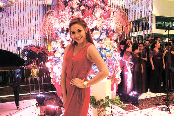 Phoebe Kaye Fernandez with Marriott's Red and Gold Christmas Tree and the Celestial Voices Chorale behind her.