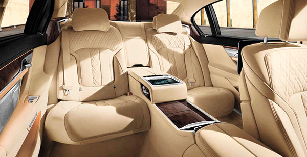 """REAR EXECUTIVE LOUNGE SEATING. The interiors of the 2016 BMW 7-Series goes beyond functional comfort-based seating, footrests, and plush floor mats. With the standard WiFi hotspot, mobile devices can directly stream content to the 10"""" entertainment screens."""