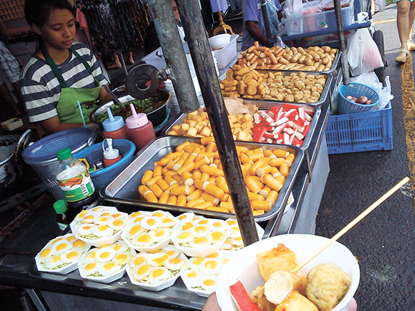 Dumplings, sausages and eggs at a street food stall in Chatuchak Weekend Market in Bangkok