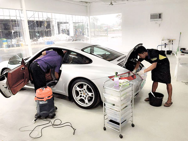 Employees working on interior detailing in Nice Day! Carwash's air-conditioned Auto Detailing Studio. (Photo by Caryl Manayo/USJ-R Communication intern)
