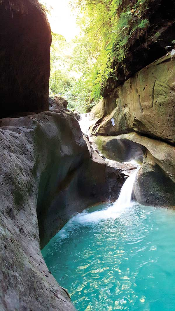 WANT TO TAKE A DIP? A trail that passes through a turquoise pool formed by a stream leads to the majestic Dau Falls, one of the 12 accessible waterfalls in the southern Cebu town of Samboan. The natural pool teems with freshwater fish.