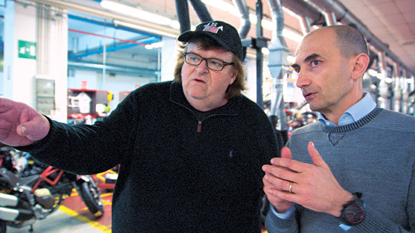 """Director Michael Moore, left, and Claudio Domenicali, CEO of Ducati, in a scene from his documentary, """"Where to Invade Next."""" (AP PHOTO)"""