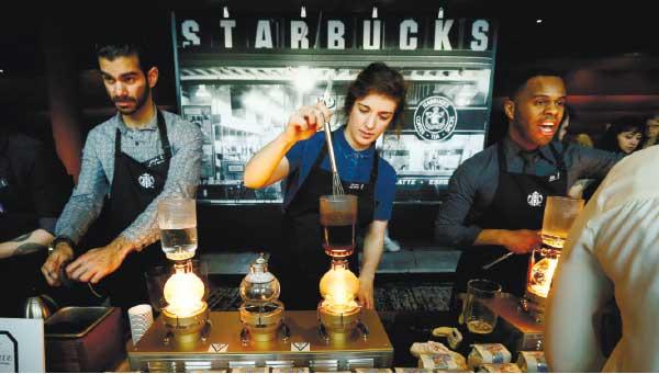 COFFEE TIME. Starbucks workers prepare coffee using siphon vacuum coffee makers. (AP PHOTO)