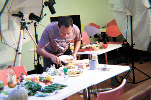 Food stylist prepares the dish. This is a normal set when shooting food.
