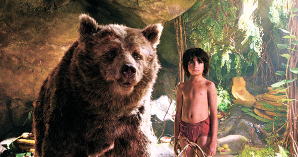 """Mowgli, portrayed by Neel Sethi, and Baloo the bear, voiced by Bill Murray, appear in a scene from, """"The Jungle Book."""" (AP PHOTO)"""
