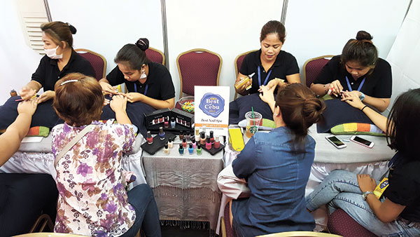 Aestheticians pamper a row of guests at the booth of Best Nail Spa Beauty and Butter.