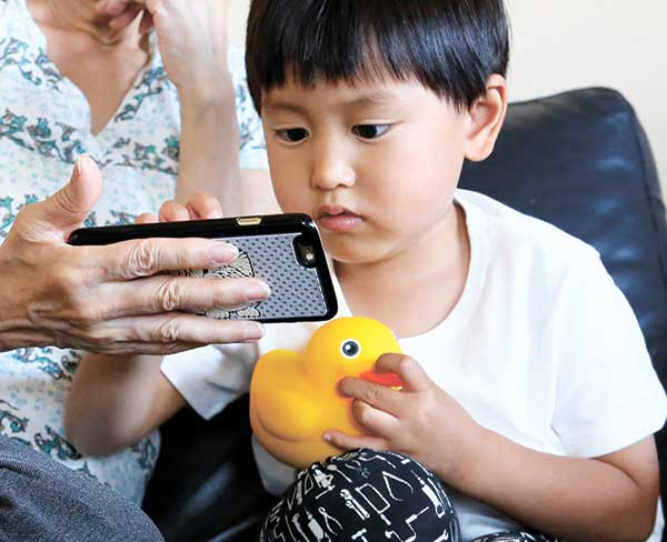 SMART DUCK. A four-year-old boy plays with Edwin the Duck, a digital duck toy, in the living room of his home in Tokyo, as his grandmother looks on. (AP PHOTO)