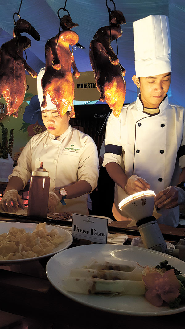 Chefs of Grand Majestic Restaurant, adjudged as having the Best Value Buffet, prepare peking duck spring rolls at their booth.