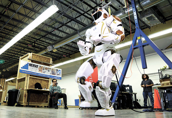 """VANGUARD. Researchers watch a six-foot-tall, 300-pound Valkyrie robot walk slowly at University of Massachusetts-Lowell's robotics center in Lowell, Massachusetts """"Val,"""" one of four sister robots built by NASA, could be the vanguard for the colonization of Mars by helping to set up a habitat for future human explorers. NASA spokesman Jay Bolden says the agency aims to get to Mars by 2035 and it'll be the Valkyries or their descendants paving the way. (AP PHOTO)"""