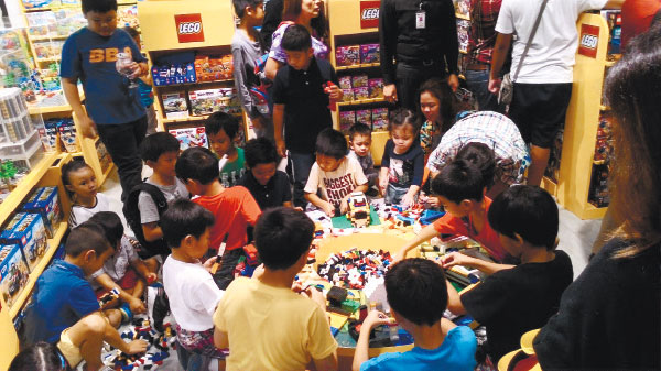 SERIOUS CREATIVITY. Kids get down and serious with piles of lego bricks and pieces during the opening of the Rustan's Lego Corner. (Photo by Carmel Matuguina)