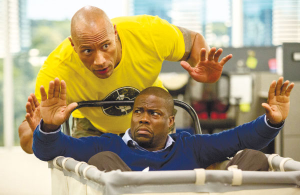 """This image released by Warner Bros. Entertainment shows Kevin Hart (bottom) and Dwayne Johnson in a scene from, """"Central Intelligence."""" (Claire Folger/Warner Bros. Entertainment Inc. via AP)"""