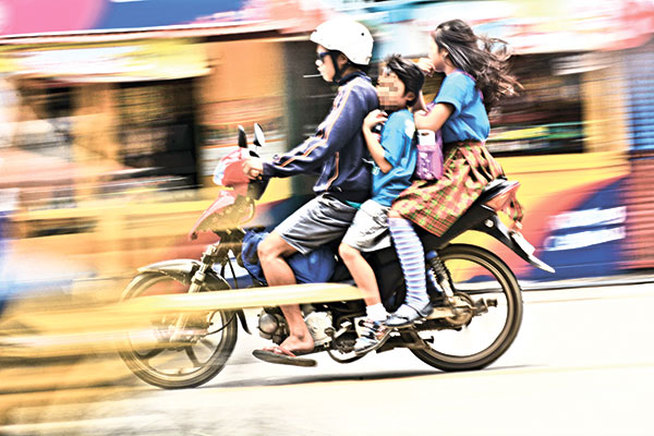"""RISKY RIDE. Children without helmets riding a motorcycle, a clear violation of Republic Act. 10666, or the """"Children's Safety on Motorcycles Act of 2015."""" (SUN.STAR FILE)"""