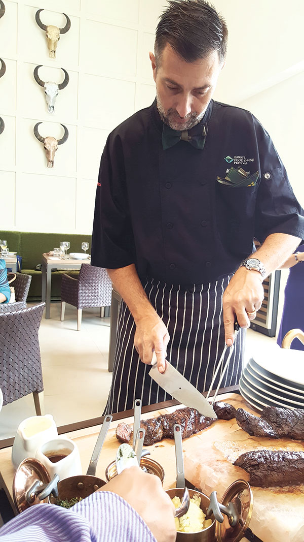 Chef Marco Anzani delicately slices a slab of Black Angus MB3 flat iron hanging tender steak prepared from a Himalayan salt block.
