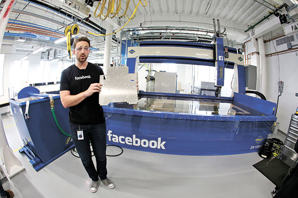 ROLE MODEL MAKER. Model maker Spencer Burns holds up a piece of sheet metal while standing in front of a water jet during a tour of Area 404, the hardware R&D lab, at Facebook headquarters in Menlo Park, California. (AP Photo/Eric Risberg)