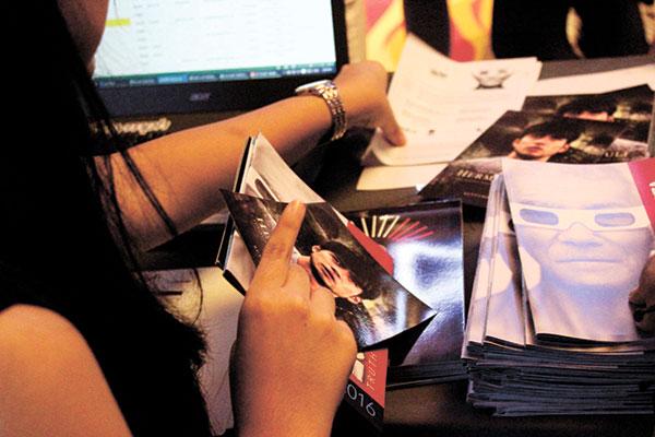 Dakila volunteer preparing the tickets for the festival
