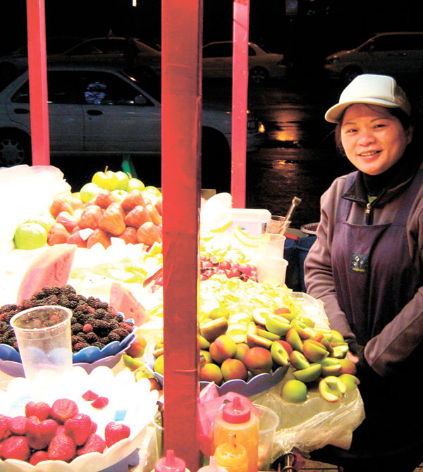 Vendor selling a variety of fruits on the sidewalk